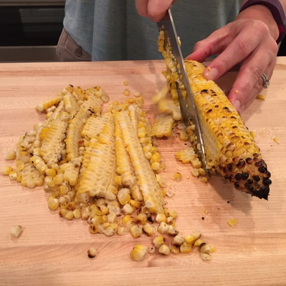 slicing off kernels while holding the cob against a cutting board is still kind of messy, but not nearly as messy as slicing them off while holding the cob vertically (thanks, melissa clark!)